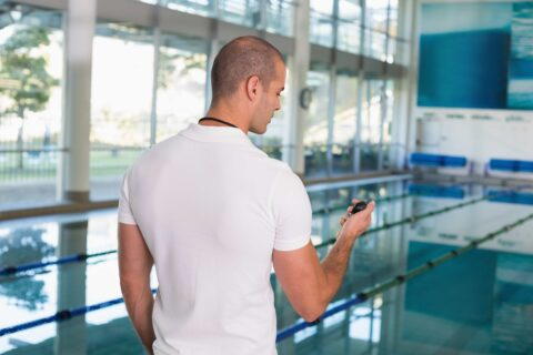 swimming-coach-looking-at-his-stopwatch-by-the-PWSWGND